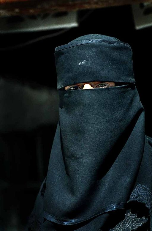 A women from yemen with a Niqaab, an englisch scrabble word with q without u following
